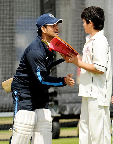 Sachin Tendulkar and his son share a moment during India's practice session