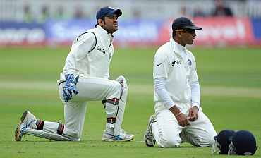 MS Dhoni (L) and Rahul Dravid react after dropping Jonathan Trott