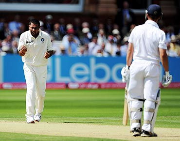 Praveen Kumar (left) celebrates after dismissing Jonathan Trott (right)