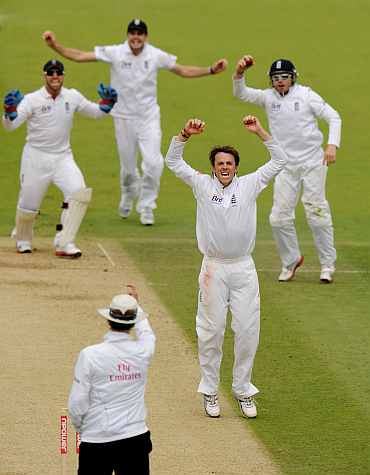 Graeme Swann celebrates after picking up Raina