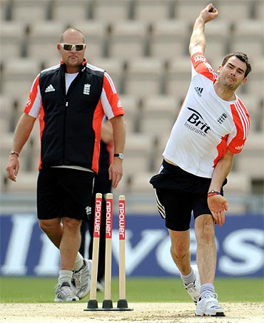 England's James Anderson bowls watched by bowling coach David Saker (L) during a training session before Thursday's third cricket
