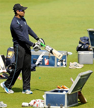 Sri Lanka's injured captain Tillakaratne Dilshan (R) holds a bat next to Duleep Mendis during a training session before Thursday's third cricket test match against England at the Rose Bowl