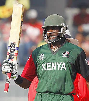 Collins Obuya raises his bat after reaching his half century