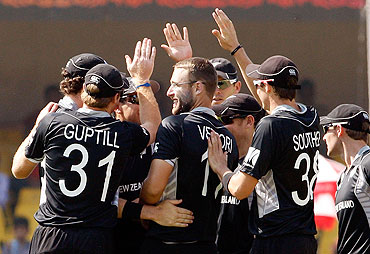 Captain Daniel Vettori of New Zealand is congratulated by teammates after getting the wicket of Regis Chakabva