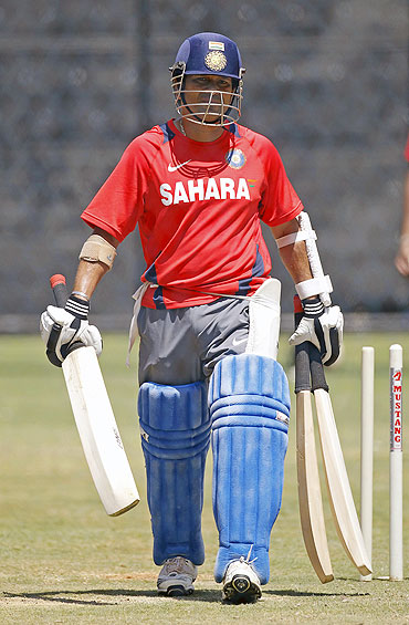 Sachin Tendulkar carries his bats to the nets during a practice session in Bangalore on Saturday