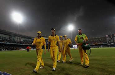 Australia's players walk off the field as rain lashes the ground