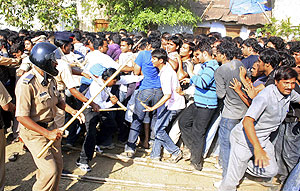 Police officers wielding sticks try to control a crowd of fans outside the Vidarbha Cricket Association Stadium in Nagpur on Tuesday