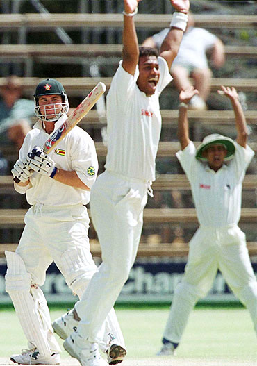 Sri Lankan bowler Ravindra Pushpakumara bowls to Zimbabwe's Alistair Campbell in a Test match in 1999