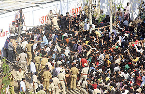 A crowd of fans rushes towards ticket windows as police try to control them outside the Vidarbha Cricket Association Stadium in Nagpur on Tuesday