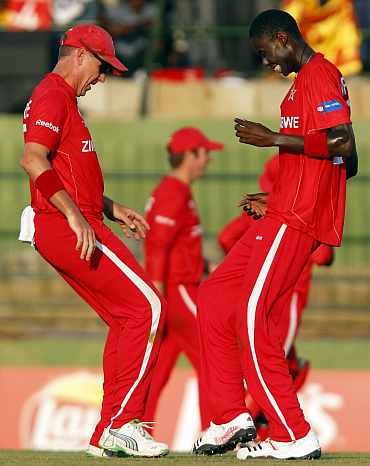 Zimbabwe's Ray Price (L) and Chris Mpofu celebrate after dismissing Sri Lanka's Upul Tharanga