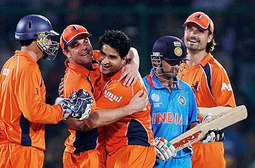 Dutch player Mudassar Bukhari (centre) celebrates with captain Peter Borren after dismissing India's Gautam Gambhir