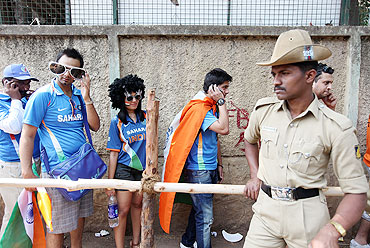 Security forces look on as fans queue outside the M. Chinnaswamy Stadium stadium in Bangalore