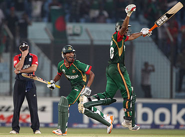 Shafiful Islam and Mahmudullah of Bangladesh celebrate scoring the winning runs as Andrew Strauss of England holds his head in his hands