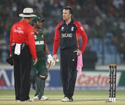 Graeme Swann has words with umpire Daryl Harper about the wet ball