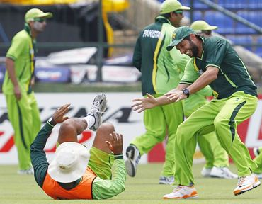 Pakistan captain Shahid Afridi (R) laughs after tackling coach Waqar Younis (C) during a practice session