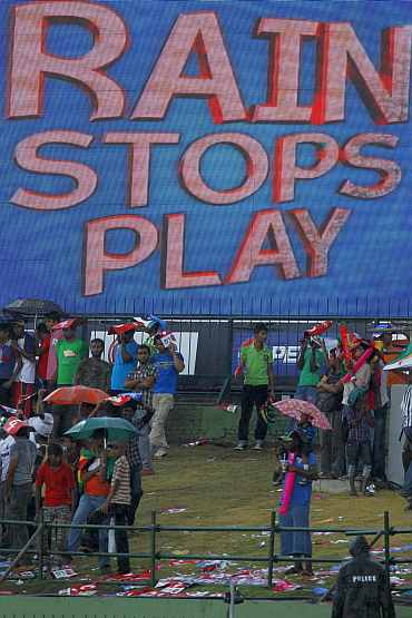 Spectators wait as rain stops play during the World Cup match between Pakistan and Zimbabwe in Pallekele