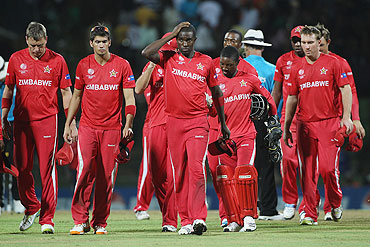 Zimbabwe captain Elton Chigumbura (3rd from left) leads his dejected players off after their seven wicket defeat against Pakistan on Monday