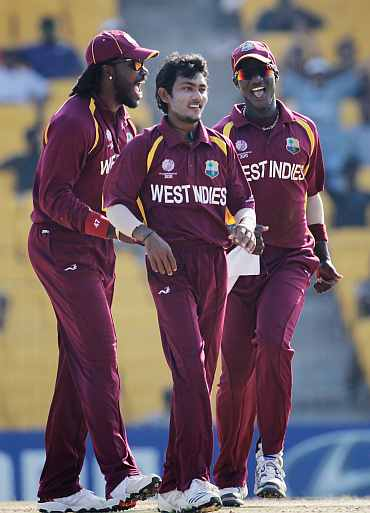 Devendra Bishoo (C) celebrates with team mates Chris Gayle and Darren Sammy