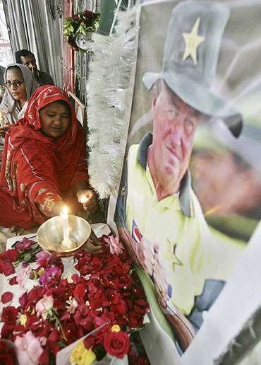 A Pakistani Christian peace activist places a rose in front of a picture of cricket coach Bob Woolmer during a memorial service in Islamabad in 2007