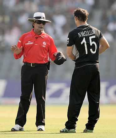 Umpire Asad Rauf talks to Nathan McCullum