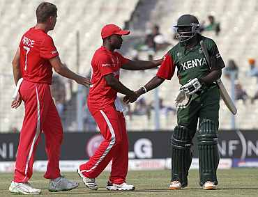 Kenya's Tikolo shakes hands with Kenya's Utseya and Price as he leaves the field following his dismissal