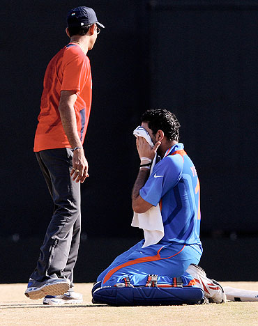Yuvraj Singh (centre) is attended to by Team India's physio Dr Nitin Patel