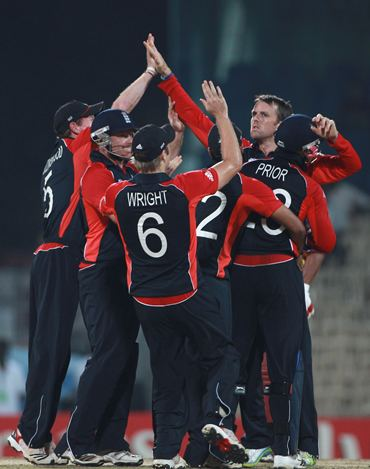 Graeme Swann is congratulated by teammates after claiming a wicket