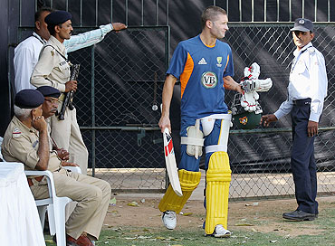 Australia's Michael Clarke walks past policemen during a nets session at Sardar Patel Stadium, Ahmedabad on Tuesday