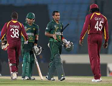 Pakistan's Mohammad Hafeez and Kamran Akmal shake hands with West Indies players after winning their match