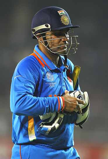 Virender Sehwag walks back to the pavillion after being dismissed by Shane Watson