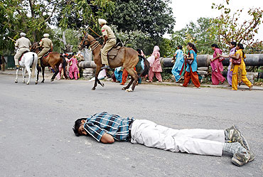 An injured man lies on a road as police mounted on horseback charge at protesters in Mohali