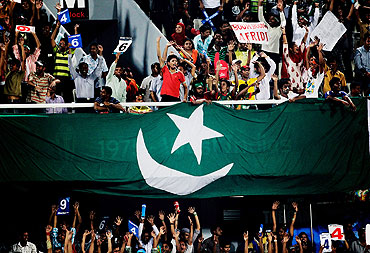 Fans celebrate as a Pakistan flag is draped over a balcony in Dhaka during Pakistan's quarter-final against West Indies