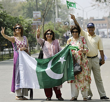 Fans hold Pakistan's national flags as they arrive in India through the India-Pakistan joint check post at the Wagah border