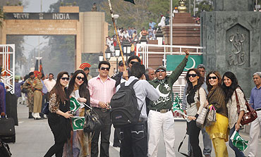 Pakistani cricket fans pose for a photographer before crossing the Wagah border on Tueday