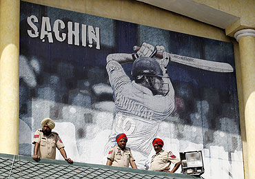 Policemen keep watch in front of a poster featuring India's Sachin Tendulkar in Mohali on Tuesday
