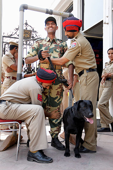 Indian security forces and their dogs are checked as they turn up to work at the Punjab Cricket Association Ground on Tuesday