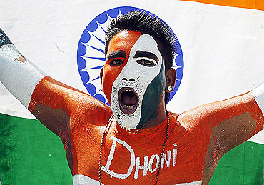 An Indian cricket fan cheers at the start of the match