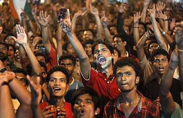 Fans react as they watch the ICC World Cup semi-final match between India and Pakistan on a screen in Mumbai