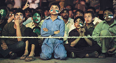 Young Pakistani cricket fans watch the semi-final between India and Pakistan on a roadside in Karachi on Wednesday