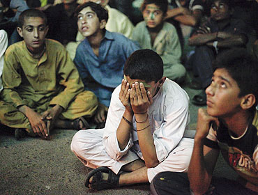 Young Pakistani cricket fans put on a dejected look after Pakistan's loss to India while sitting below a screen along a roadside in Karachi