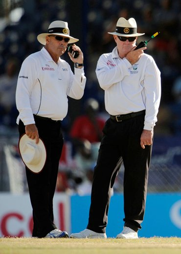 Umpires Daryl Harper (L) and Russell Tiffin (2nd L) wait for a referral verdict