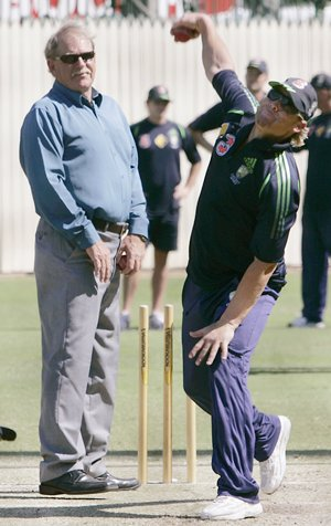 Warne (R) bowls in the nets, watched by Jenner