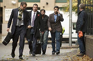 Salman Butt (second right) speaks on the phone as he arrives at Southwark Crown court on Thursday