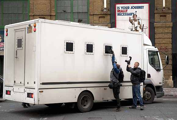 Photographers take pictures through the window of a prison van as it leaves Southwark Crown court in London