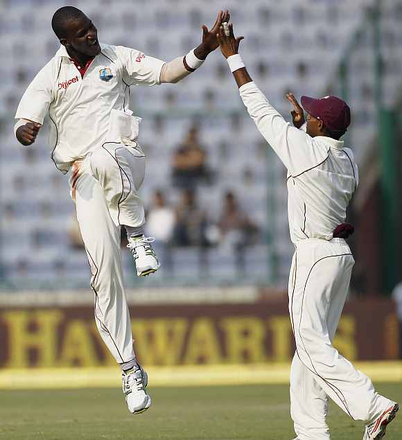 West Indies' Darren Sammy celebrates with Chanderpaul after picking up a wicket