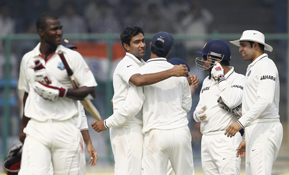 India's Ravichandran Ashwin (2nd L) celebrates with his team mates after dismissing West Indies' captain Darren Sammy (L) during the third day of their first test cricket match in New Delhi