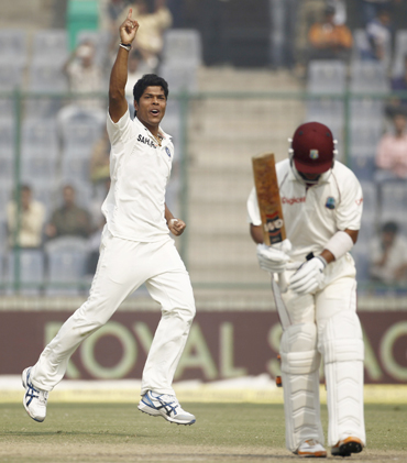 India's Umesh Yadav celebrates after dismissing West Indies Carlton Baugh (R) during the third day of their first test cricket match in New Delhi
