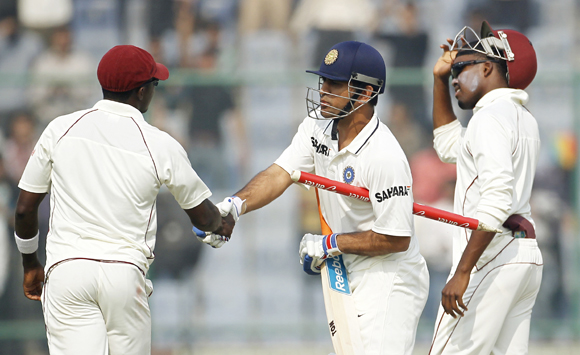 India captain Mahendra Singh Dhoni (C) shakes hands with West Indies' Fidel Edwards (L) as Darren Bravo watches after India won the first Test