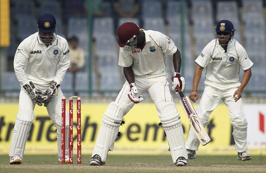 Sammy is clean bowled by R Ashwin as M S Dhoni and Gautam Gambhir watch, during the first Test