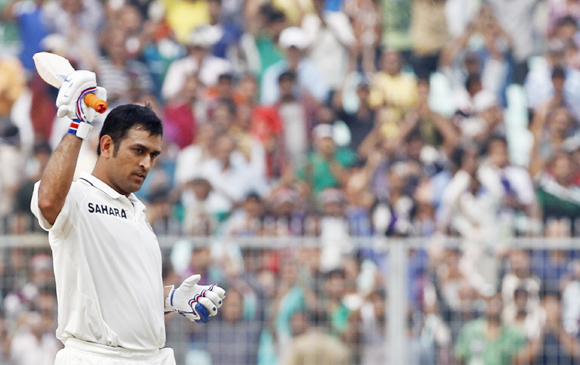 India's captain Mahendra Singh Dhoni raises his bat to celebrate his century